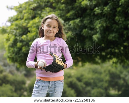 Girl standing in park with baseball and glove, smiling, front view, portrait - stock photo