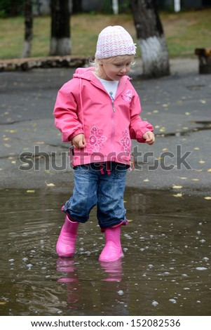 girl standing in puddles  - stock photo