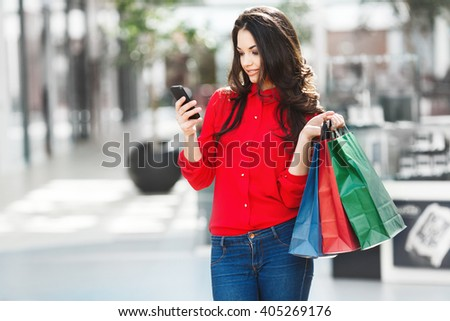 Girl standing in shopping mall, looking at phone. Beautiful girl holding colorful shopping bags in one hand and phone in other hand. Both hands raised. Wearing red blouse and jeans. Indoor - stock photo