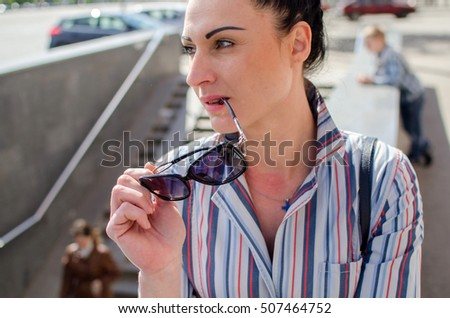 girl standing leaning to the fence and taking her sunglasses off