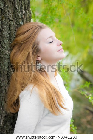 girl standing near a tree, summer, sunny weather - stock photo