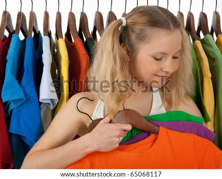 Girl standing near the rack of colourful clothing, choosing clothes to guy. - stock photo