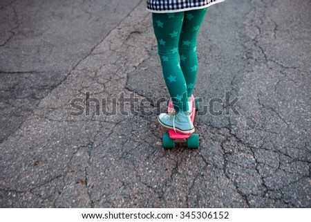 Girl standing on a pink skateboard outdoors - stock photo