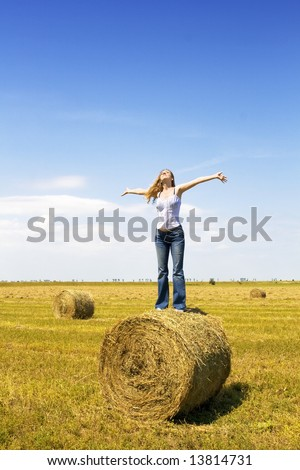 girl standing on a straw roll spreading her hands towards the sky - stock photo