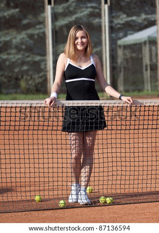 Girl standing on a tennis court for lessons with balls. - stock photo