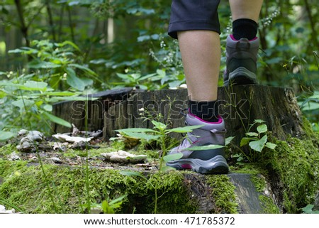 Girl standing on a tree stump, hiking boots in focus