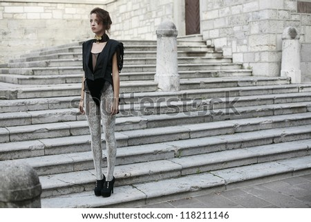 girl standing on old stairs - stock photo