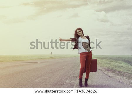 girl standing on road with suitcase votes and looks for fellow traveler