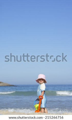 Girl (3-5) standing on sandy beach with bucket and spade, side view, sea in background