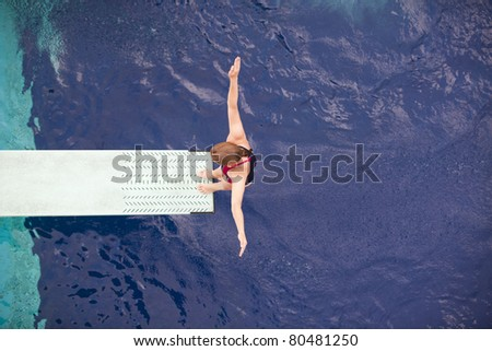 Girl standing on springboard - stock photo