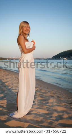 girl standing on the beach in a cape