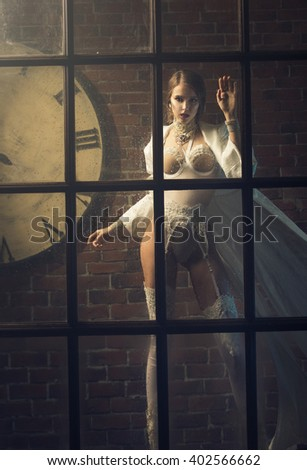 Girl standing on the street in the rain, looking out the window - stock photo