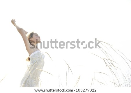 Girl standing with arms outstretched against the open sky at the beach. - stock photo