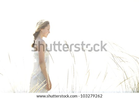 Girl standing with long grass against the open sky at the beach. - stock photo