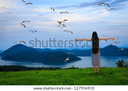 Girl standing with open arms against the blue sky, Freedom concept - stock photo