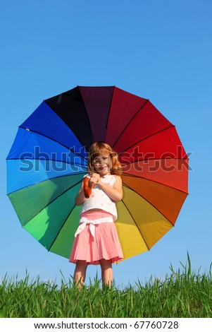 girl stands in meadow with green grass against blue sky and holding colored umbrella - stock photo