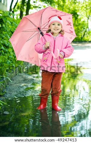 girl stands in the puddle with umbrella