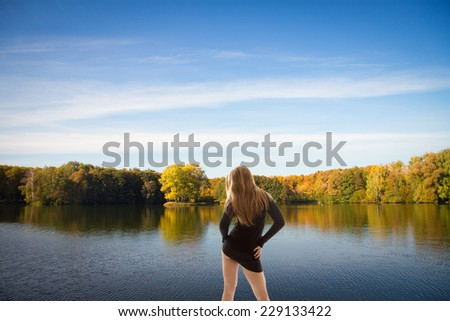 girl stands near the river. golden autumn on the lake. everything was yellow in the fall. - stock photo