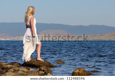 Girl stands on a rock and looking at sea - stock photo