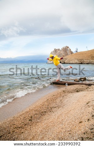 girl stands on the shore of Lake Baikal