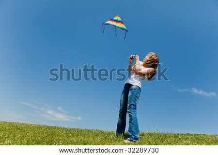 Girl starts a kite standing on a green grass