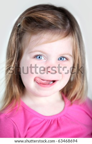 Girl sticking out tongue and licking her lips - stock photo