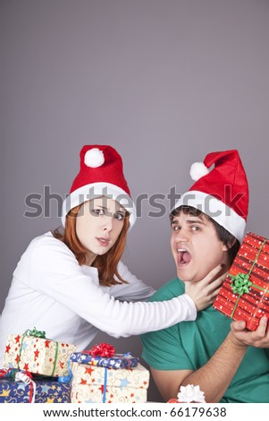 Girl strangling her boyfriend for a christmas gift. Studio shot.