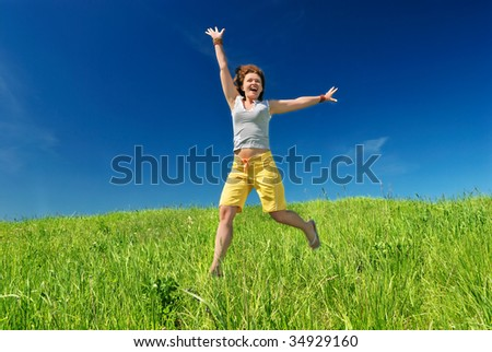Girl stratching hands on the field under sun - stock photo