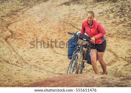 Girl struggling with her bike on a sandy track in northern Madagascar