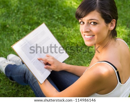 Girl student reading book outside in park. Happy caucasian hispanic college student smiling and looking at camera. - stock photo
