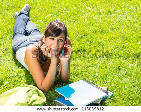 Girl student talking by cell phone in a park. Happy cute brunette lying down on grass with notebooks outside. Copy space. - stock photo