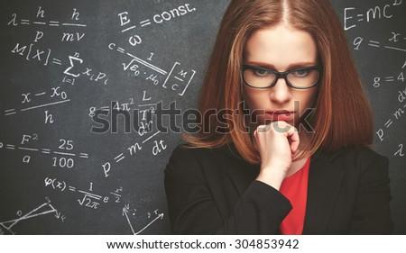 girl student, the teacher writes on the blackboard chalk formula - stock photo