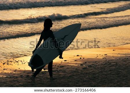 girl surfer  on seashore at sunset in Doninhos beach Galicia - stock photo