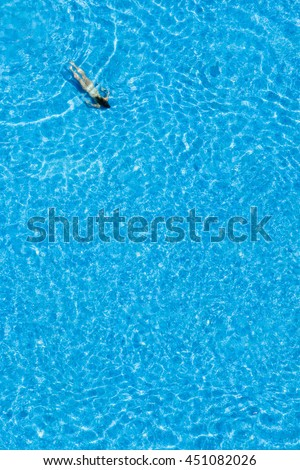 Girl swim in the swimming pool at the hotel. View from above.