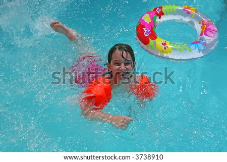 Girl Swimming Along in Blue Pool Water - stock photo