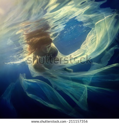 Girl swims underwater with a cloth. - stock photo