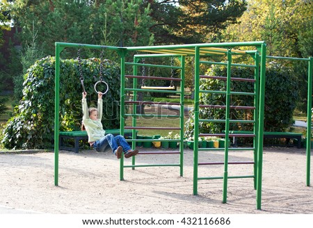 girl swinging on the rings Playground in the yard