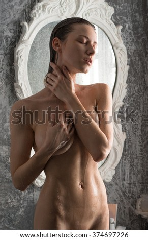 Girl takes a morning shower near the vintage mirrors - stock photo