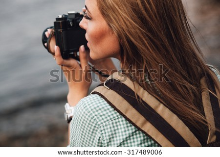 Girl takes photographs with vintage photo camera outdoor