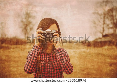 Girl takes photographs with vintage photo camera outdoor. Vintage image - stock photo