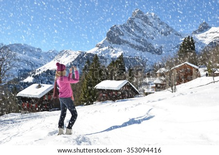 Girl taking a photo in the Swiss Alps - stock photo