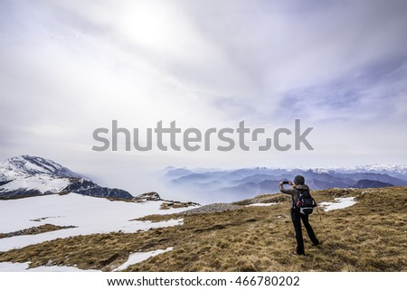 Girl taking a picture in the middle of a field with some snow at Monte Altissimo, San Giacomo, Trentino region, Italy