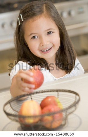 Girl taking apple from fruit basket at home - stock photo