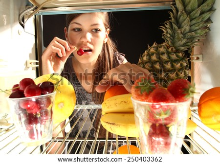 girl taking fruits from the fringe