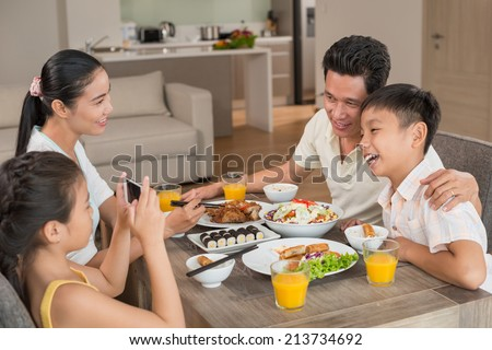 Girl taking photo of her father and brother at the dinner table