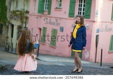 Girl taking photo of her friend in Paris, France - stock photo