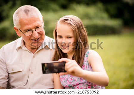 Girl taking photo with mobile phone of herself and her grandfather - stock photo