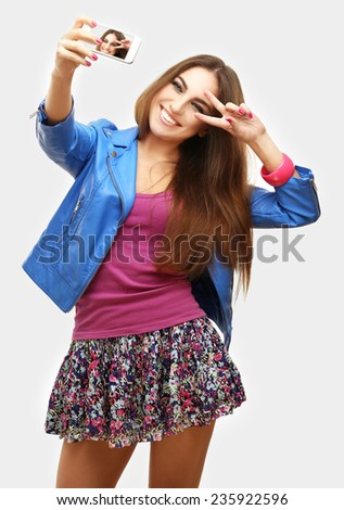 Girl taking photos of herselves on smart phone - stock photo