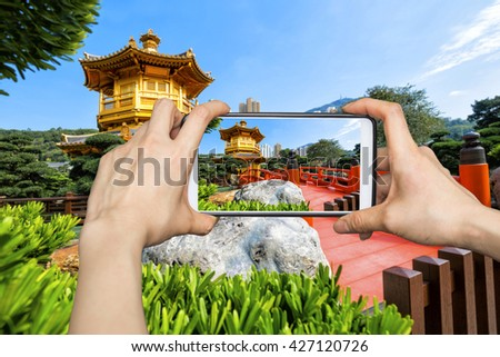 Girl taking pictures on mobile smart phone in Front View The Golden Pavilion Temple in Nan Lian Garden - stock photo