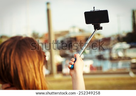 girl taking selfie picture outdoors.Focus on phone